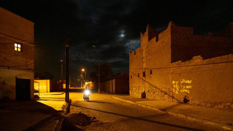 Ein Motorradfahrer auf einer nächtlichen, leeren Straße in der kleinen marokkanischen Stadt Mhamid, am Rande der Sahara